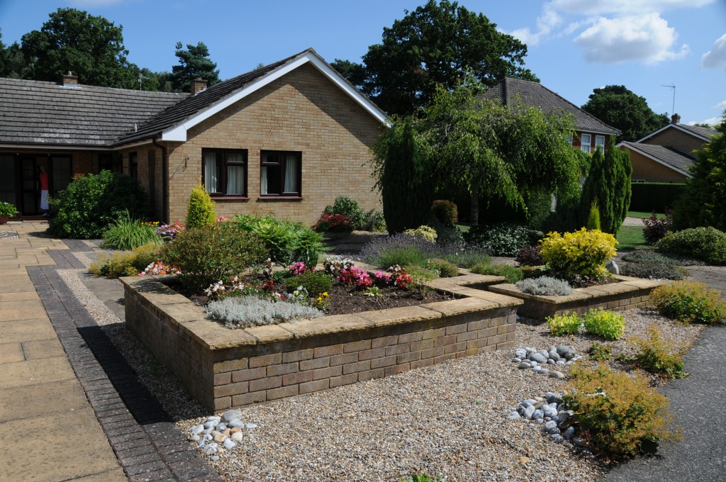 Raised brick planters in a large front garden, planted with various shrubs and shingle around the planters.