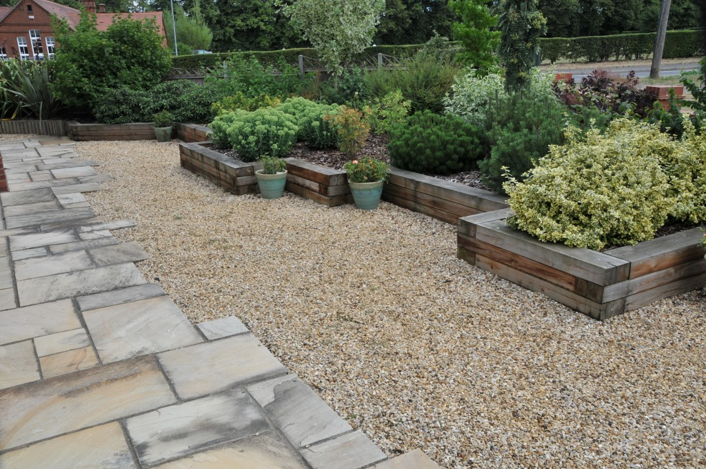 A railway sleeper bed enhances most gardens, together with carefully selected shrubs.