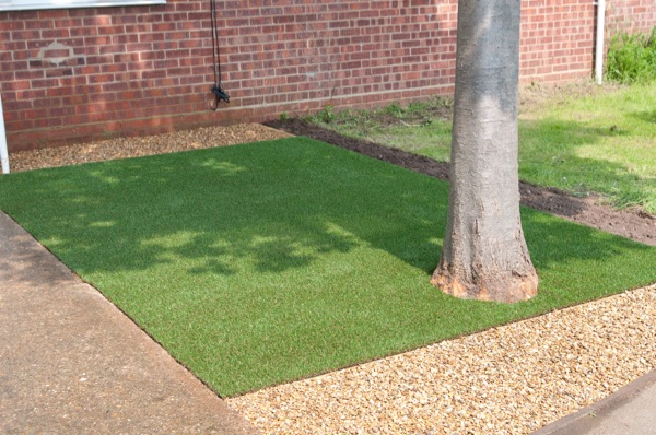 Artificial turf with a tree and surrounding shingle